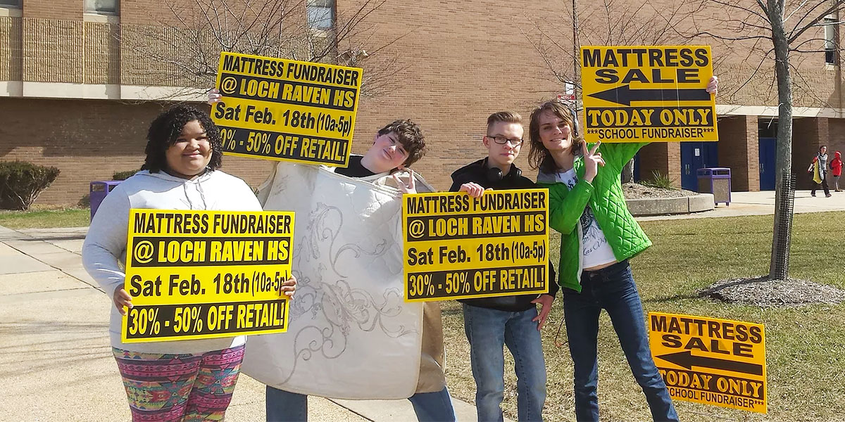 Students Holding Signs for the Mattress Fundraiser